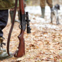 Picture of rifle and hunters waiting for hunting to begin.