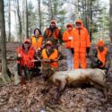 Group of Hunters around Trophy Elk